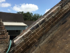 Repointing bricks on the roof of a historic building on a plantation