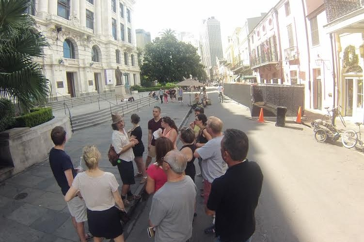 A group listens to the NOLA Tour Guy in front of the Appeals Court in the French Quarter, New Orleans